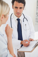 Doctor pointing at clipboard while talking to patient