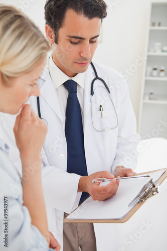 Doctor and his patient looking at clipboard together