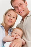 Close up of smiling parents with their baby