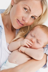 Close up of woman holding her sleeping baby