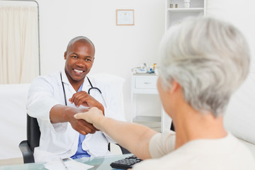 Smiling doctor shaking his patients hand