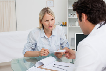 Worried woman getting prescription from her doctor
