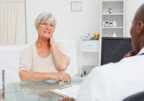 Mature woman telling her doctor about her neck pain