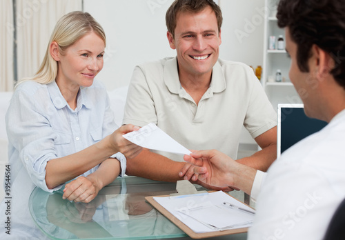 Doctor giving prescription to happy couple