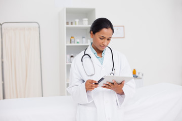 Young serious doctor standing in a hospital room while looking at her tablet pc