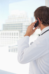 Rear view of a young doctor talking on the phone
