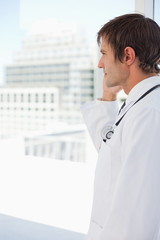 Side view of a surgeon talking on the phone in front of a window