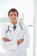 Smiling doctor standing upright while crossing his arms