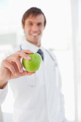 A surgeon is holding a delicious green apple