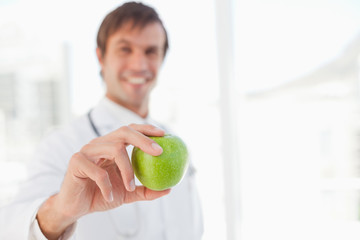 Beautiful green apple held by a surgeon