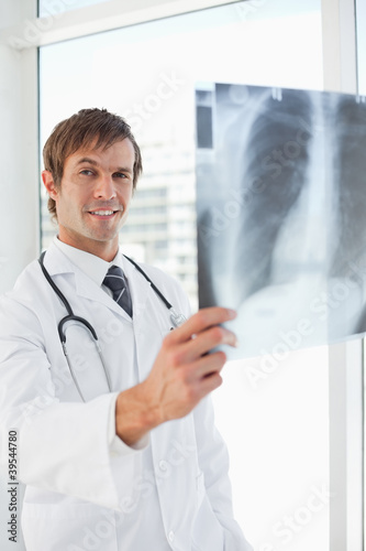 Young smiling doctor holding a chest x-ray
