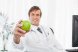 Green apple being held by a relaxed doctor
