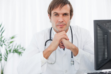 Serious doctor looking at the camera while placing his hands in front of his chin