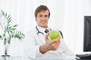 Smiling surgeon sitting at his desk while holding a green apple