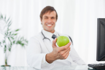 Beautiful green apple being held by a happy doctor