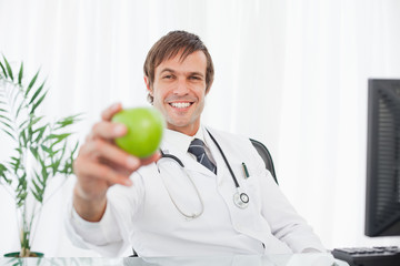 Smiling surgeon holding a green apple while sitting at the desk