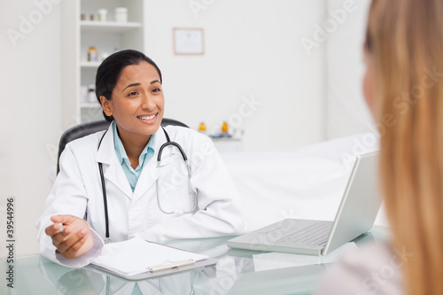 Practitioner sitting a desk with a clipboard and a laptop while talking to a patient