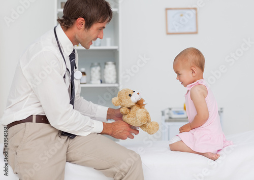 Smiling doctor offering a teddy bear to a little baby