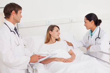 Serious doctor placing her hand on her patient while talking to her