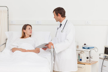 Relaxed patient lying in a bed while talking to her doctor
