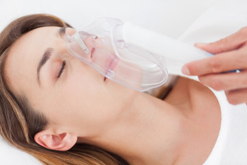 Young woman closing her eyes while breathing through an oxygen mask