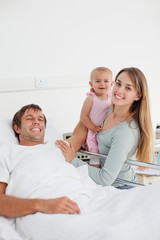 Patient lying in a hospital bed while his wife and his baby are standing next to him