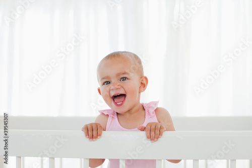 Beautiful baby standing in her bed while shouting