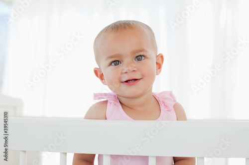 Lovely baby looking at the camera while standing in her bed