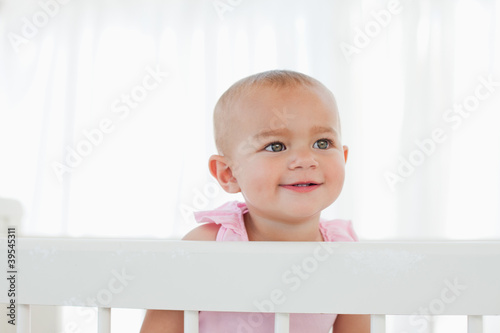 Smiling baby looking towards the side while standing in her bed