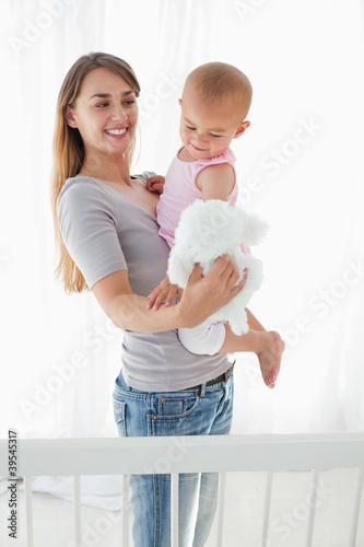 Smiling mother holding her baby and a white teddy