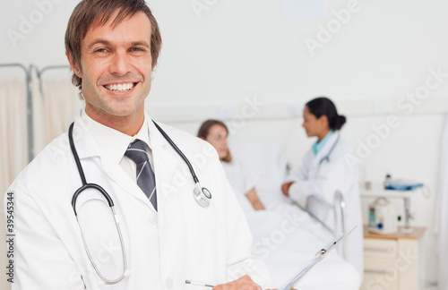 Smiling doctor holding a clipboard while standing in a hospital room