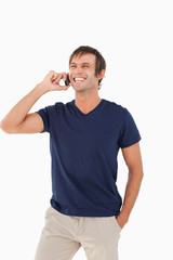 Laughing man talking on the phone while placing his hand in his pocket