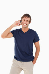 Smiling man standing upright with his hands in his pockets while talking on the phone