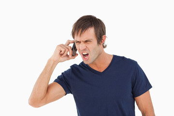 Furious man using his cellphone while shouting