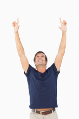 Smiling man showing his happiness by raising his arms above his head