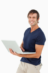 Smiling man holding a laptop while looking at the camera