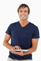 Smiling man holding a tablet pc while looking at the camera