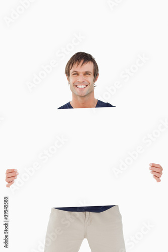 Smiling man holding a blank poster