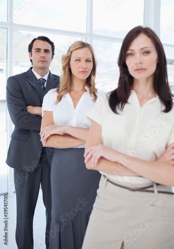 Three serious colleagues standing behind each other with their arms crossed
