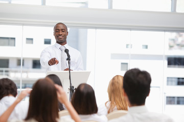 Businessman pointing towards a member of an audience