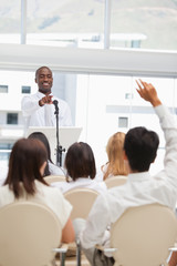 Businessman smiling as he points towards a member of the audience