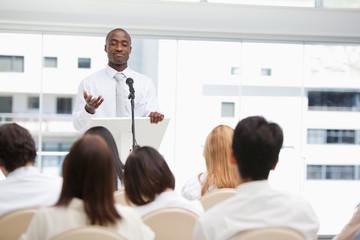 Businessman gesturing towards an audience