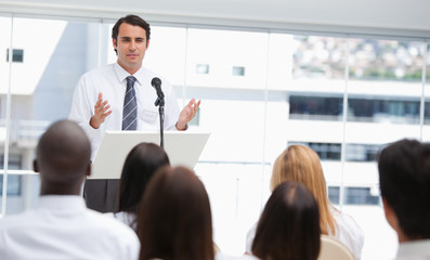 Black haired businessman gesturing towards an audience