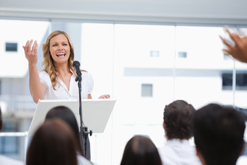 Businesswoman laughing while gesturing towards a member of an audience