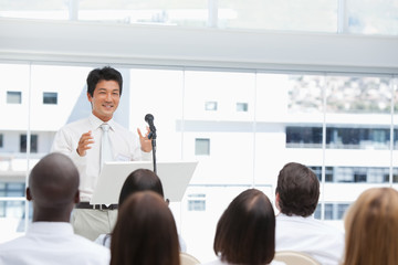 Businessman smiling as he gestures to an audience who are watching him