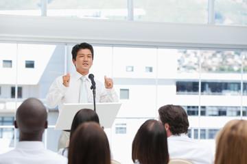 Serious businessman gesturing towards an audience