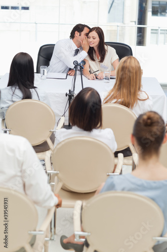 Businessman whispers to his colleague as they are being watched by an audience