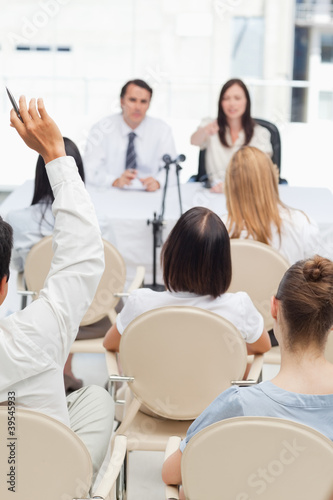 Man raising his hand while watching two business people
