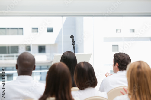 Colleagues sit while watching a microphone
