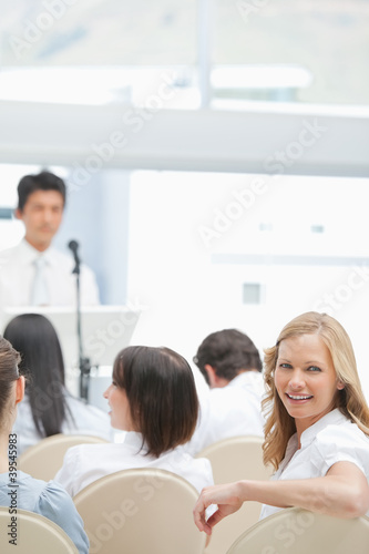 Close-up of a smiling woman looking behind her during a presentation